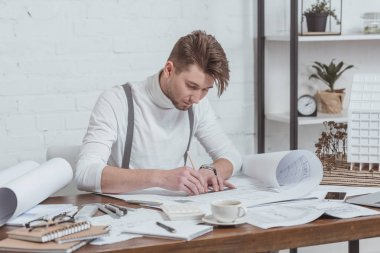portrait of focused architect working on sketches at workplace in office
