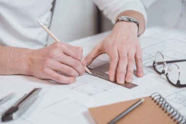 cropped shot of architect with ruler and pencil working on project at workplace in office