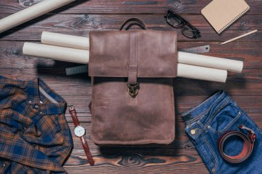 flat lay with male shirt, jeans, watch and blueprints in backpack arranged on wooden tabletop