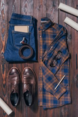 flat lay with male shirt, shoes, jeans, eyeglasses and architectural blueprints arranged on wooden surface