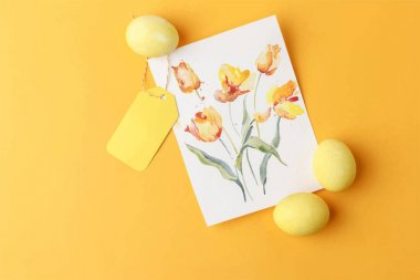 Top view of card with painted flowers near empty label and Easter eggs on yellow background clip art vector