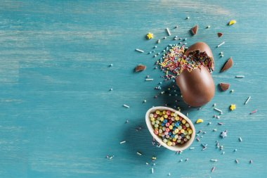 top view of chocolate egg with Easter sprinkles on blue wooden table