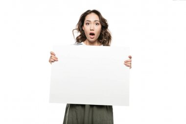 Shocked young woman holding blank white card and looking at camera stock vector