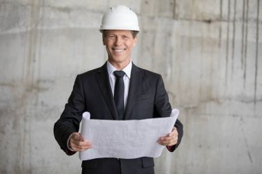 Professional architect in hard hat holding blueprint and smiling at camera stock vector