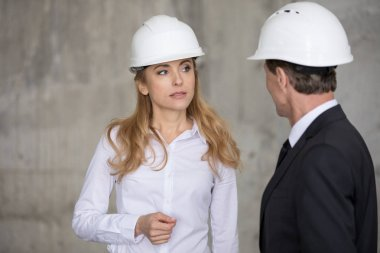 Serious blonde engineer in hard hat looking at colleague at construction site stock vector