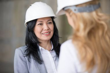 Smiling professional architect in hard hat looking at blonde colleague while working stock vector
