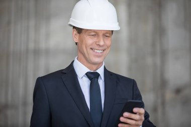 Smiling middle aged businessman in hard hat using smartphone stock vector