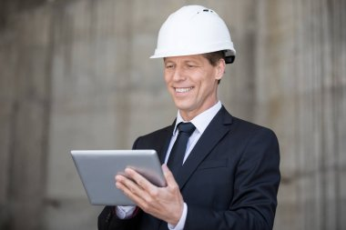 Smiling middle aged businessman in hard hat using digital tablet stock vector