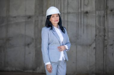 Confident middle aged asian businesswoman wearing hard hat and looking at camera stock vector