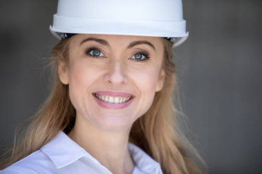 Beautiful blonde businesswoman in hard hat smiling at camera stock vector