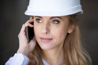 Close-up portrait of confident blonde businesswoman in hard hat talking on smartphone and looking away stock vector