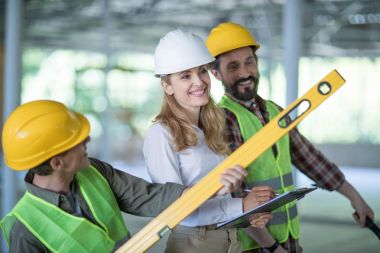 Smiling inspector writing on clipboard while standing with workers holding level tool stock vector