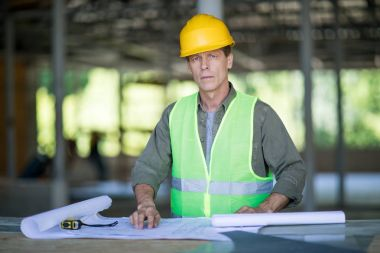 Serious engineer in hard hat working with blueprints and looking at camera stock vector