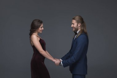 sweethearts in evening outfit holding hands