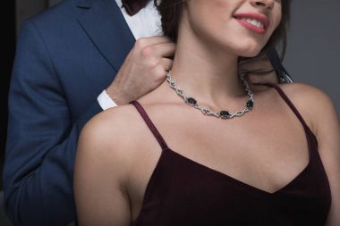 man in tuxedo putting necklace on girlfriend