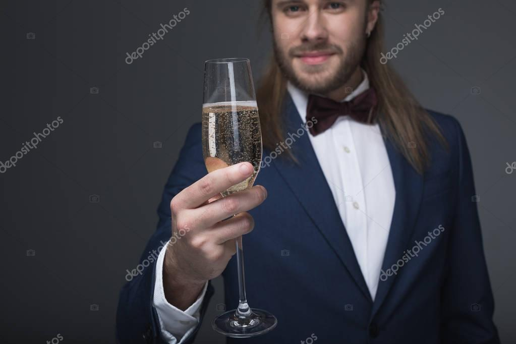 man in tuxedo holding glass with champagne