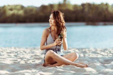 Woman drinking beer on beach