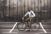 Stylový muž sedí na kole