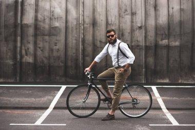 stylish man sitting on bicycle
