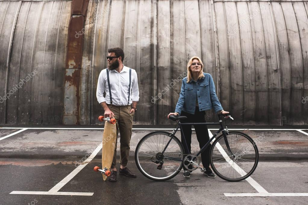 stylish couple with bicycle and longboard