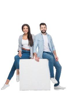 Couple sitting on cube