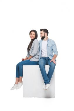 Couple sitting on cube