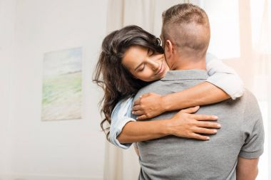 happy couple hugging at home