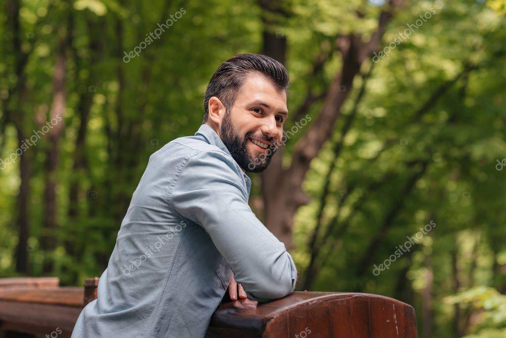Man standing on wooden bridge
