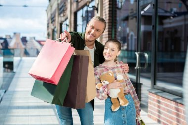 Portrait of smiling man with shopping bags in hand showing something to daughter stock vector