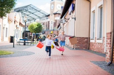 children running with shopping bags