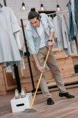 Mann fegt Fußboden in Boutique