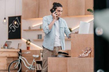 shop owner talking on smartphone