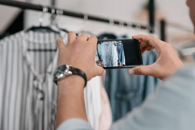 Close-up partial view of young man photographing clothes with smartphone stock vector
