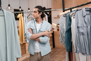man working with clothes in boutique