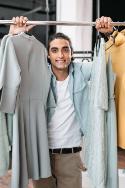 Handsome young shop owner standing between clothes and smiling at camera stock vector