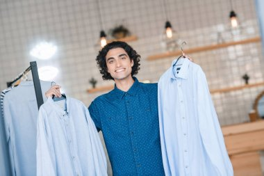 man choosing shirts in boutique