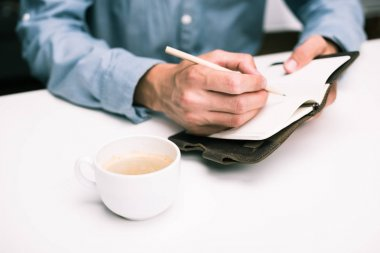 man writing in diary