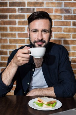 Man drinking coffee with sandwich