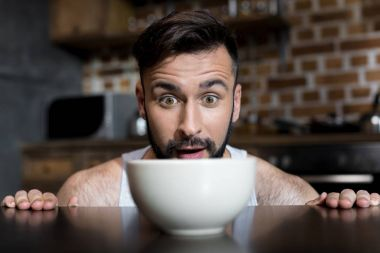 bearded young man looking at breakfast