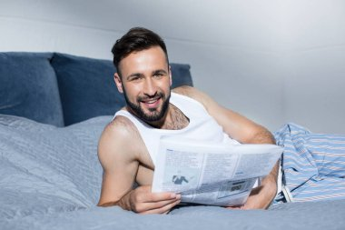 bearded man reading newspaper in bed