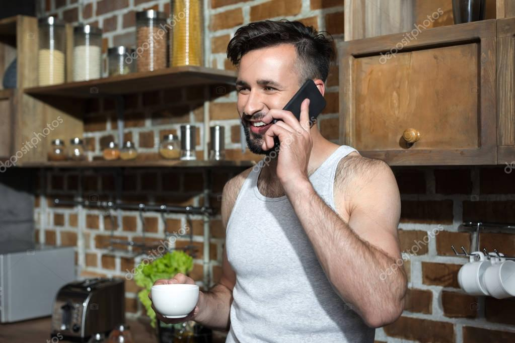 man with coffee talking on smartphone