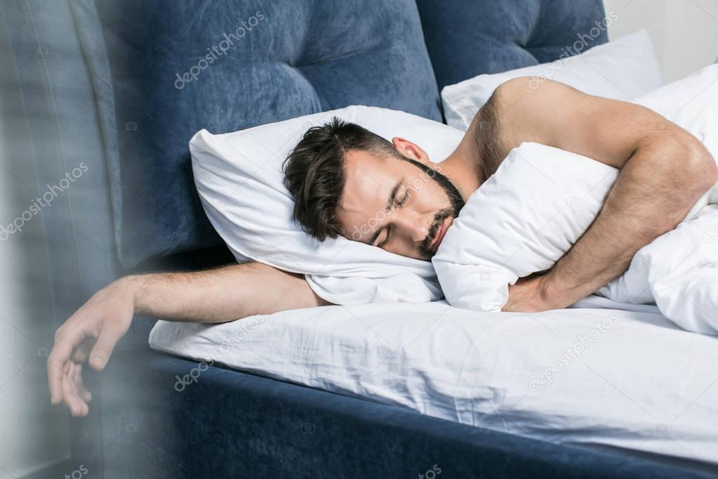 Handsome young man sleeping in bed — Stock Photo