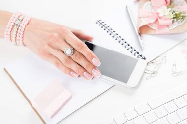 female hand with smartphone at workplace