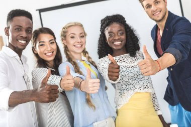 multiethnic businesspeople showing thumbs up