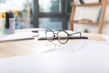 Eyeglasses on workplace with papers