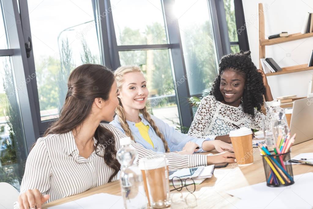multiethnic businesswomen talking in office
