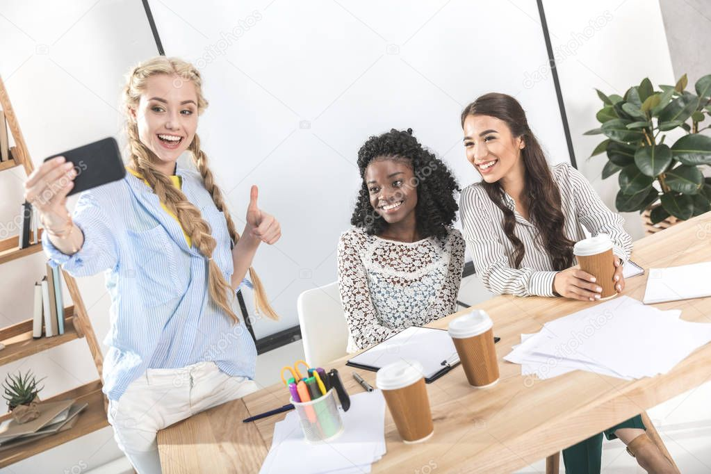 Multicultural smiling businesswomen taking selfie on smartphone at workplace
