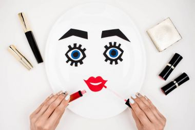 Cropped view of female hand applying lipgloss on paper face with makeup on plate, isolated on white, beauty concept stock vector