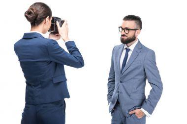 woman taking photo of businessman