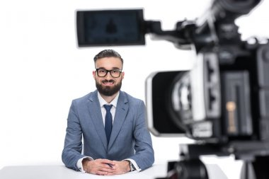 newscaster sitting in front of camera